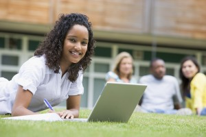 Young woman using laptop on campus lawn, with other students rel