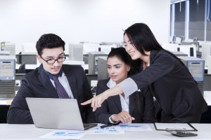 Portrait of businesswoman explaining the business plan on the laptop to her partners in the office